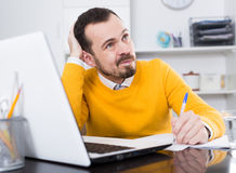 Man facing difficulty. Young male student having complicated issue at online courses at home Royalty Free Stock Image
