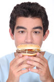 Man facing a hamburger Stock Photos