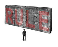 Man facing red rule word on huge concrete puzzles connected. Man facing red rule word on four huge concrete puzzles connected together, isolated on white Stock Images