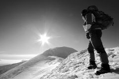 Man facing the sun. In winter time, through the snow on the crest of the mountain Royalty Free Stock Photos