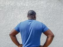 Rear view of man standing confidently with hands on waist, posing with arms akimbo and thinking royalty free stock images