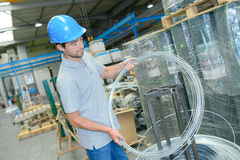 Man in factory holding roll wire. Man in factory holding roll of wire Royalty Free Stock Image