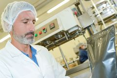 Man in factory with sealed bag. Factory royalty free stock images