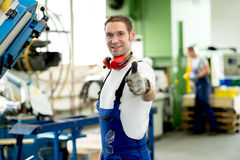 Man in factory with thumb up. Friendly man in factory with thumb up stock photo