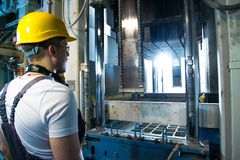Man on a factory. Worker in safety hat near machine on a factory royalty free stock photos
