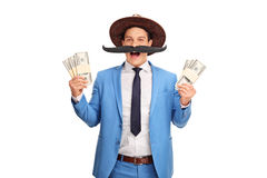 Man with a fake moustache holding money. Young man with a fake moustache and a cowboy hat holding few stacks of money isolated on white background royalty free stock images