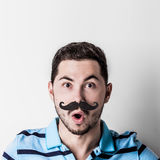 Man with fake mustache. Portrait of man with retro style fake mustache and surprised facial expression Stock Photography