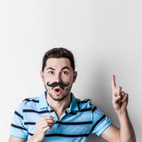 Man with fake mustache. Portrait of man with fake mustache on stick saying something important with finger up royalty free stock photos