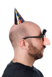 Man with fake nose and hat. Man with fake nose and party hat with mustashe and eyebrows over awhite background royalty free stock photography