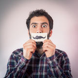 Man with fake paper moustaches Stock Images
