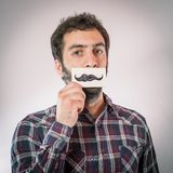 Man with fake paper moustaches Royalty Free Stock Images