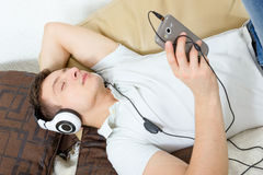 Man fall asleep listening to music over smartphone with headphon Royalty Free Stock Photography