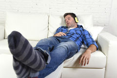 Man falling asleep on home couch while listening to music with mobile phone and headphones Royalty Free Stock Images
