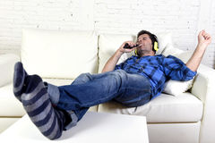 Man falling asleep on home couch while listening to music with mobile phone and headphones Stock Photo