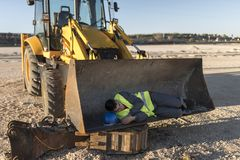Man for falling asleep on shovel of excavator. During work break Royalty Free Stock Photo