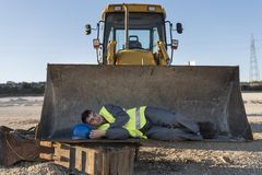Man for falling asleep on shovel of excavator. During work break Stock Images