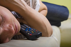 Man falling asleep with TV remote control Royalty Free Stock Photography