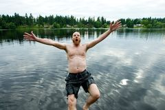 Man Falling Backwards into lake. A bald man falling backwards into the cold water of a lake Stock Photography