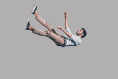 Man falling down. Mid-air shot of handsome young man falling against grey background Stock Images