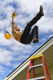 Man Falling off Roof. Man falling from edge of roof while using ladder royalty free stock images