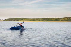 Man falling from the rubber boat to water of lake. Nature landscape Royalty Free Stock Photography