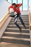 Man Falling on Stairs. Hispanic businessman falling on stairs while carrying binders stock image