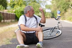 Man falls off bicycle cross on track stock photos