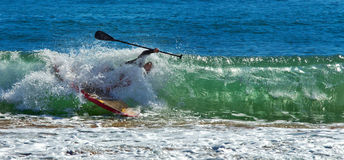 Man falls off paddleboard. Falling off a paddleboard into a big wave in the sea. Face obscured royalty free stock image