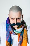 Man with false moustache and colored scarf. Man with false moustache wearing colored scarf around his neck royalty free stock photos