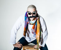 Man with false moustache and colored scarf. Man with false moustache wearing colored scarf and welding glasses sitting on a wooden stool royalty free stock images