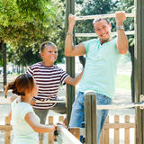 Man with family training on chin-up bar Royalty Free Stock Image
