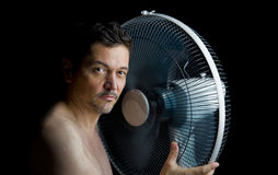 Man with fan. Heat wave - sweaty man with fan isolated on black background Royalty Free Stock Images