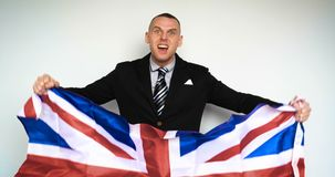 Man is a fan of the United Kingdom of Great Britain. In slow motion a guy man is a fan of the United Kingdom of Great Britain Englishman on emotions holding a stock footage