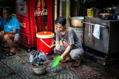 Man fanning a cooking fire in Ho Chi Minh City, Vietnam Royalty Free Stock Photo