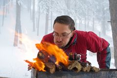 Man fanning fire in grill Royalty Free Stock Image