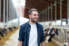 Man or farmer with cows in cowshed on dairy farm. Agriculture industry, farming, people and animal husbandry concept - happy smiling young man or farmer with Stock Images