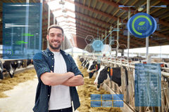 Man or farmer with cows in cowshed on dairy farm. Agriculture industry, people and animal husbandry concept - happy smiling young man or farmer with herd of cows stock images