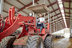 Man or farmer driving tractor at farm Stock Image