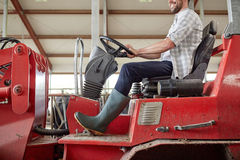 Man or farmer driving tractor at farm Stock Photography