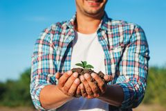 Man farmer smiling and holding young plant in hands against spring sky background. Earth day Ecology concept. Close up selective f. Ocus on Person hands with royalty free stock photography