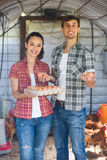 Man farmer and woman holding container with eggs Stock Photo
