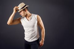 Man fashion model, stylish young man wearing fedora hat. Standing posing, over black background Stock Images