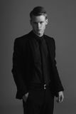 Man fashion portrait. Fashion vogue style studio portrait of young male model posing in black stylish formal suit with tie stock images