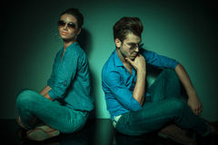 Man and fashion woman sitting back to back Royalty Free Stock Images