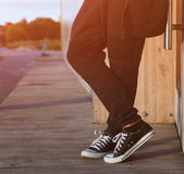 A man in a fashionable black outfit posing at the sunset of a warm summer day in sneakers. Part of the body, close-up. A man in a fashionable black outfit Stock Photo