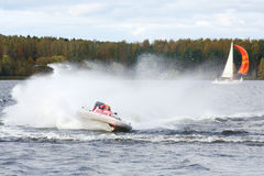 Man fast floats at power boat on river. At competitions at autumn day royalty free stock images