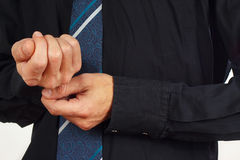 Man fastened the buttons on sleeve black shirt closeup Royalty Free Stock Photos