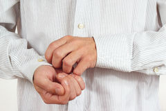 Man fastened the buttons on sleeve bright shirt closeup Stock Photos