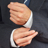 Man fastened the buttons on sleeve business suit closeup Royalty Free Stock Photography