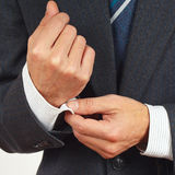 Man fastened the buttons on sleeve suit closeup Royalty Free Stock Photo